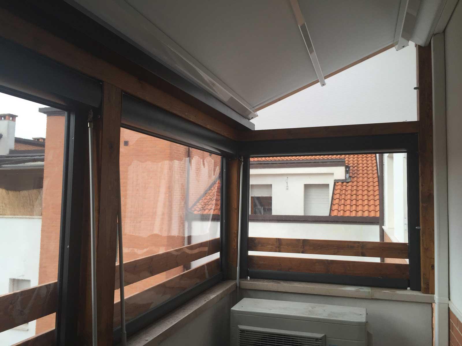 Veranda su balcone con coperto di tenda in pvc retraibile e tende termiche.